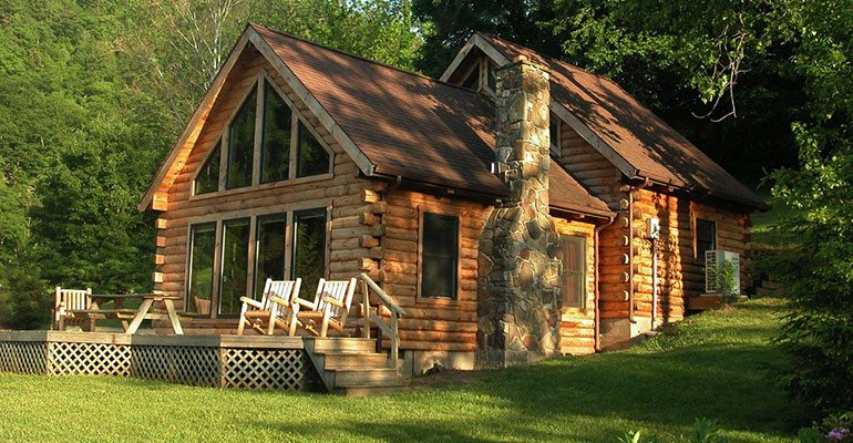 An exterior view of a large log cabin, surrounded by lush forest