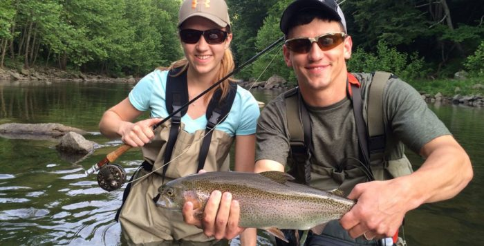 A happy couple hold up a trout