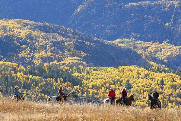 A group of people horseback riding along the West Virginia mountains